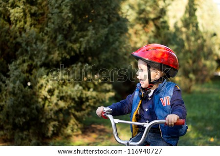 Little boy wearing a red crash helmet riding a bicycle outdoors on his own with copyspace - stock photo