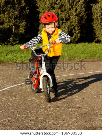 Little boy wearing a safety helmet and high visibility jacket mounting his bicycle throwing his leg over the saddle as he prepares to go out for an enjoyable ride in the evening sunlight - stock photo