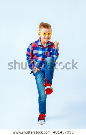 Little boy wearing colorful plaid shirt, blue jeans, gumshoes, plastic glasses having fun in the studio - stock photo
