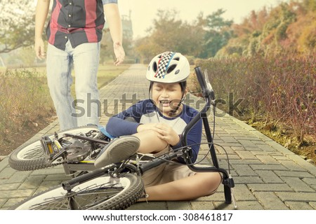 Little boy wearing helmet and crying while holding his knee after accident with his bike - stock photo