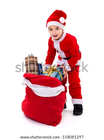 Little boy wearing Santa Claus uniform, taking out gift from bag - stock photo