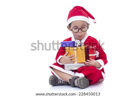 Little boy wearing Santa Claus uniform with a gift. - stock photo