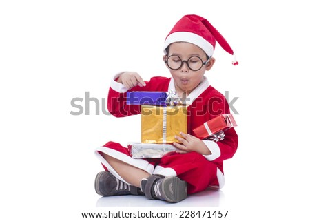 Little boy wearing Santa Claus uniform with gifts  - stock photo
