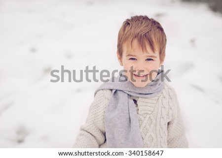Little boy wearing scarf and sweater laughing and looking kind at the camera in winter snow - stock photo