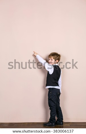 Little boy wearing school uniform. Boy pointing at wall - stock photo
