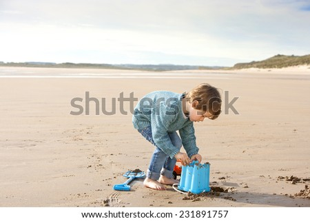 Little Boy with a Bucket building Sandcastles on the Beach - stock photo