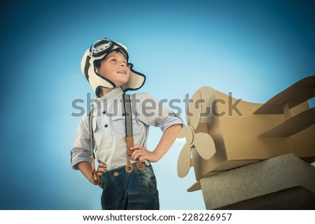 Little boy with a cardboard airplane - stock photo