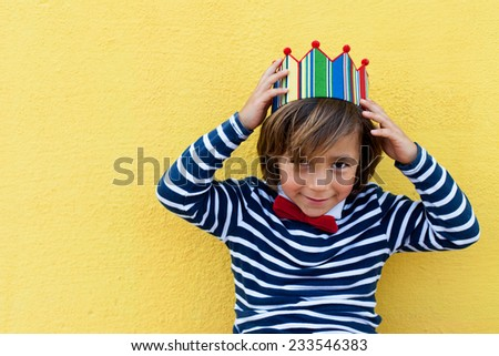 little boy with a crown, wearing a red bow tie and a stripes navy sweater.  - stock photo