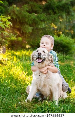 Little boy with a golden retriever outdoor - stock photo