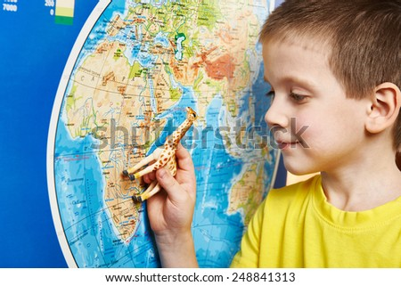 Little boy with a toy giraffe shows Africa on the world map - stock photo