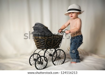 Little boy with antique stroller - stock photo