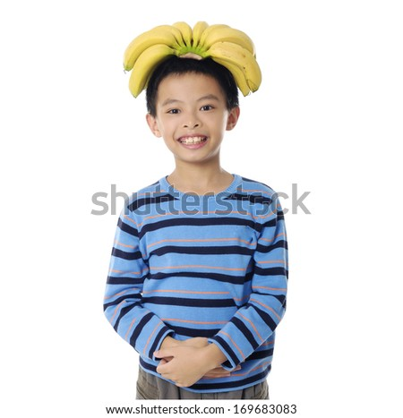 Little boy with banana on his head - stock photo