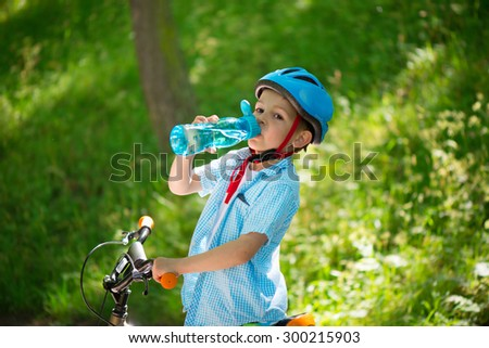 Little boy with bicycle drinks water summer in park - stock photo