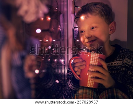 Little boy with big cup of hot drink looks on the window with Christmas Lights - stock photo