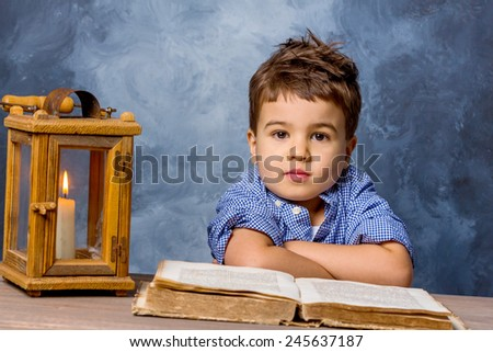 little boy with book and lanterns, symbol of education, school reform, learning - stock photo