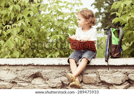 little boy with book sitting in the park at the day time - stock photo