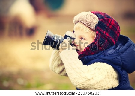 Little boy with camera is shooting in the farm - stock photo