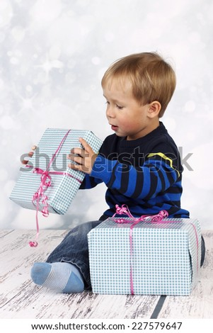Little boy with christmas presents - stock photo
