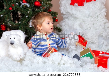 Little boy with Christmas presents near decorated fir tree - stock photo