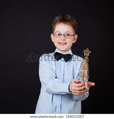 Little boy with Christmas tree over the black - stock photo