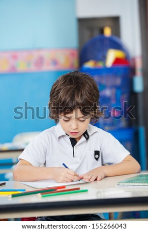 Little boy with colored sketch pens drawing in kindergarten - stock photo