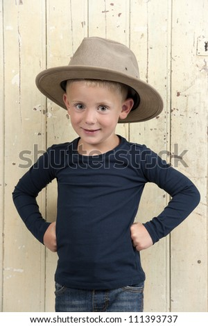 little boy with cowboy hat against an old wooden door, arms in his hips - stock photo