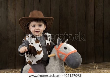 Little boy with cowboy hat on toy horse in a barn - stock photo