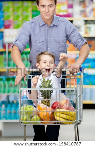 Little boy with fists up suiting in shopping trolley with food, father drives the cart - stock photo