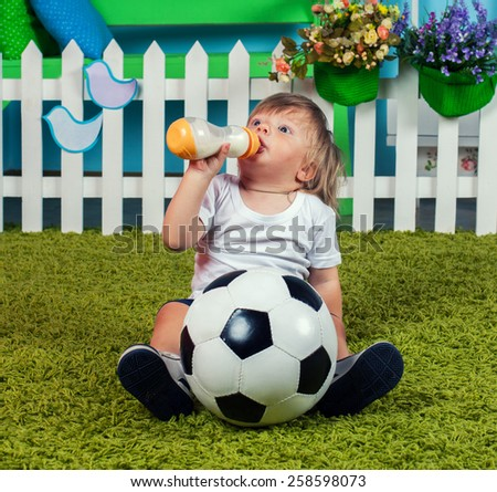 Little boy with football drinking milk from bottle with nipple - stock photo