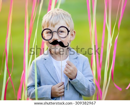little boy with funny paper mustache and glasses - stock photo
