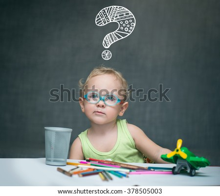 Little boy with glasses sits at a table on which are scattered crayons and toys over his head hangs a question mark - stock photo