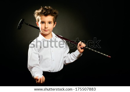 Little boy with golf club low key studio portrait  - stock photo