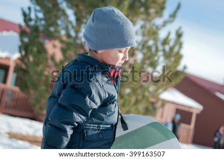 Little boy with grey toboggan carrying a sled looking down. - stock photo