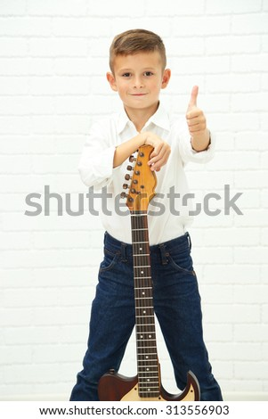 Little boy with guitar on light background - stock photo