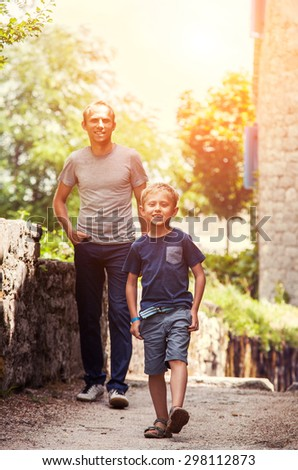 Little boy with his father walk together - stock photo