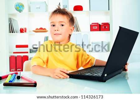 Little boy with his laptop at home. - stock photo
