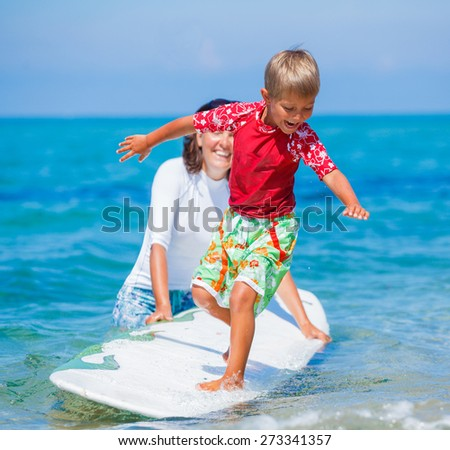 Little boy with his mother learning surfing - stock photo