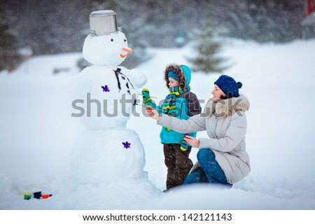 Little boy with his mother painting a snowman - stock photo