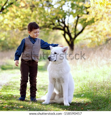 little boy with his nice white dog in park - stock photo