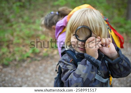 Little boy with magnifying glass in the forest - stock photo