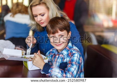 Little boy with mother in fast food restaurant behind glass - stock photo