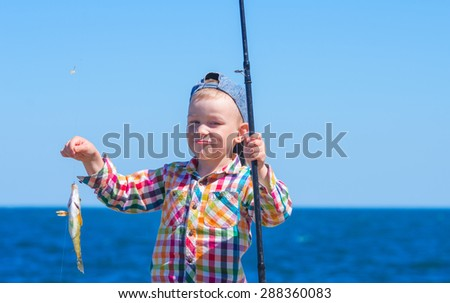 "Little boy with mysterious sight holding a fishing pole with his first catch - ""Symphodus tinca"". Family composition - stock photo"