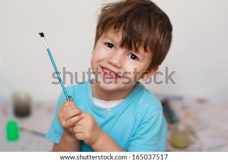 Little boy with paintbrush, preschooler painting education, childhood - stock photo