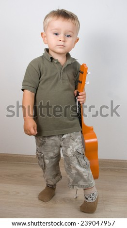 Little boy with plastic toy guitar  - stock photo