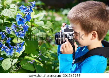Little boy with retro camera shooting of blue flowers - stock photo