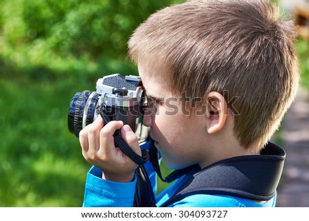 Little boy with retro camera shooting outdoors - stock photo