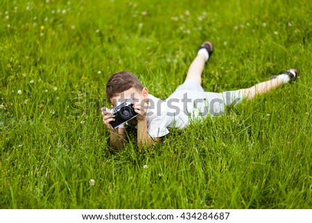 Little boy with retro photo camera shooting outdoor. Kid taking a photo using a film cam. Green summer garden. Young photographer. - stock photo