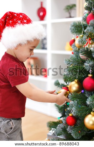 Little boy with Santa hat, decorating Christmas tree - stock photo
