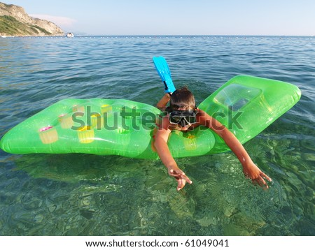 little boy with scuba diving mask and flippers swimming on green pool raft - stock photo