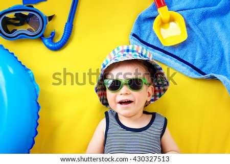 little boy with sunglasses in hat on yellow blanket - stock photo